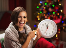 Smiling young woman near christmas tree pointing on clock Stock Photos