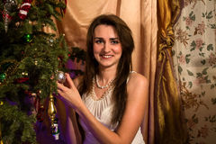 Smiling Young Woman near Christmas tree Royalty Free Stock Photos