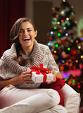 Smiling young woman near christmas tree with present box Royalty Free Stock Photos