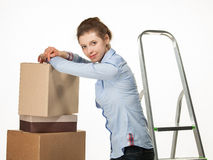 Smiling young woman near a pile of boxes Stock Photo