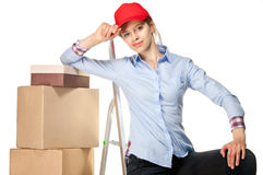 Smiling young woman near a pile of boxes Royalty Free Stock Photos