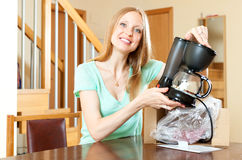 Smiling young woman with new electric coffee maker at home behin Royalty Free Stock Photos