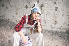 Smiling woman in newspaper hat holding paint bucket. Repair home concept. Royalty Free Stock Photos