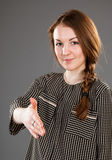 Smiling young woman offering handshake to you. Grey background Royalty Free Stock Images