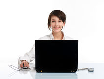 Smiling young woman in the office. Young woman in the office sitting at the table, in front of the notebook, on white background royalty free stock photos