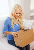 Smiling young woman opening cardboard box at home. Home, post, delivery and happiness concept - smiling young woman opening cardboard box at home Stock Photos