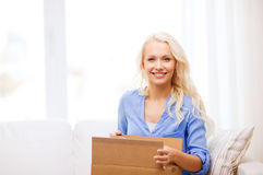 Smiling young woman opening cardboard box Stock Photo
