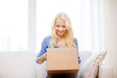 Smiling young woman opening cardboard box royalty free stock image