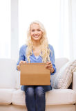 Smiling young woman opening cardboard box Royalty Free Stock Photography
