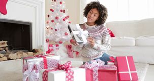 Smiling young woman opening her gifts at Christmas stock video