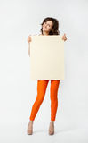 Smiling young woman in orange pants holding blank placard Royalty Free Stock Image