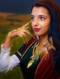Smiling  Young woman with ornamental dress and hand jewel. Natural background. Stock Photos