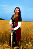 Smiling Young woman with ornamental dress and sword in hand  standing on a wheat field with sunset. Natural background.. Smiling Young woman with ornamental Stock Photo
