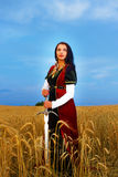 Smiling Young woman with ornamental dress and. Sword in hand  standing on a wheat field with sunset. Natural background Stock Photography