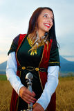 Smiling Young woman with ornamental dress and sword in hand  with sunset. Natural background.. Stock Images