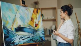Smiling young woman painter is taking on mobile phone standing near her picture in workshop holding brush. Communication stock video footage