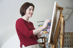Smiling young woman painting. Stock Photos