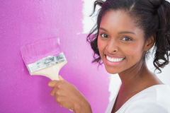 Smiling young woman painting her wall in pink Royalty Free Stock Images