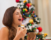 Smiling young woman in pajamas eating cookies Royalty Free Stock Photo
