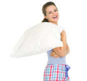 Smiling young woman in pajamas holding pillow Stock Images