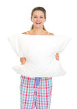 Smiling young woman in pajamas holding pillow Royalty Free Stock Photography