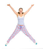Smiling young woman in pajamas jumping Stock Photography