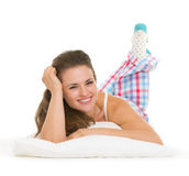 Smiling young woman in pajamas laying on pillow Royalty Free Stock Photos