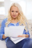 Smiling young woman with papers at home Stock Photography