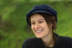 Smiling Young Woman in Park. Smiling young Caucasian woman with a blue gatsby cap in a park (Selective Focus, Focus on the left eye Royalty Free Stock Images