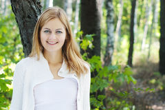 Smiling young woman in a park Royalty Free Stock Photography