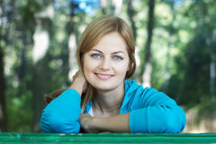 Smiling young woman in a park Stock Photography