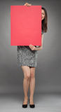Smiling young woman peeping out through a red placard Stock Image