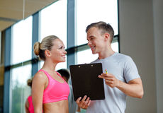 Smiling young woman with personal trainer in gym Stock Images