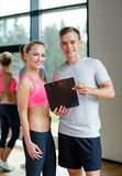 Smiling young woman with personal trainer in gym Stock Image