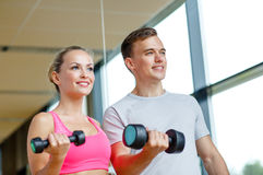 Smiling young woman with personal trainer in gym Royalty Free Stock Image
