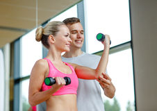 Smiling young woman with personal trainer in gym Royalty Free Stock Images