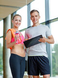 Smiling young woman with personal trainer in gym Stock Photography