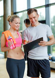 Smiling young woman with personal trainer in gym Royalty Free Stock Photos