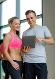 Smiling young woman with personal trainer in gym Stock Photos