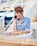 Smiling young woman on phone with laptop in modern office Stock Photos