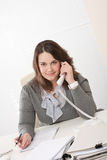 Smiling young woman on the phone at office Stock Images