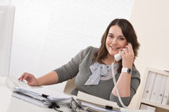 Smiling young woman on the phone at office Stock Photo