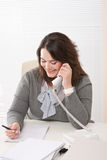 Smiling young woman on the phone at office Royalty Free Stock Images