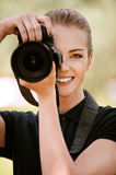 Smiling young woman photographs on Stock Image