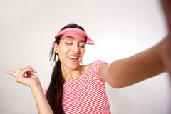 Smiling young woman with pink cap taking selfie Stock Images