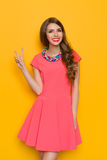 Smiling Young Woman In Pink Dress Showing Peace Sign Royalty Free Stock Photo
