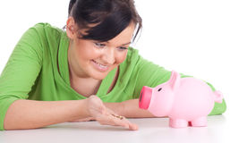 Smiling young woman with pink piggy bank Stock Images