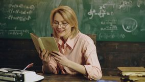Smiling young woman in a pink shirt is reading a book near a green chalkboard with formulas written on it. Young pretty. Blonde girl student before class stock video