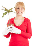 Smiling young woman with plant Stock Images