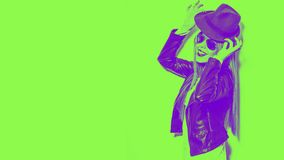 Smiling young woman playing with hat, wearing sunglasses black leather jacket green and purple colors stock images